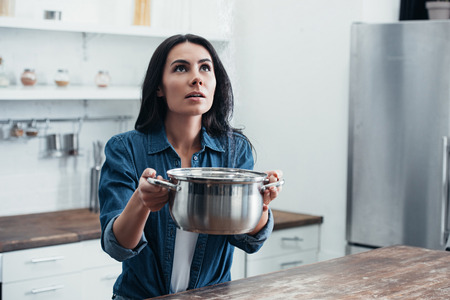 Woman in denim shirt holding steel pot and looking up Stock Photo