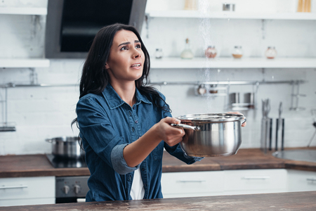 Stressed young woman using steel pot during water leak in kitchen