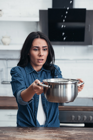 Worried pretty woman with pot dealing with water leak in kitchen