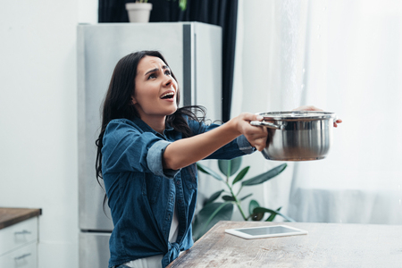 Worried woman in denim short with pot dealing with water damage in kitchen