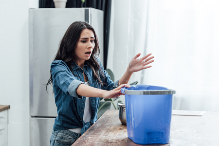 Upset young woman using bucket during leak in kitchen Imagens