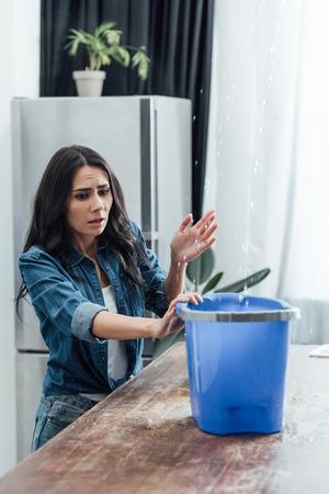 Worried woman using bucket during leak in kitchen