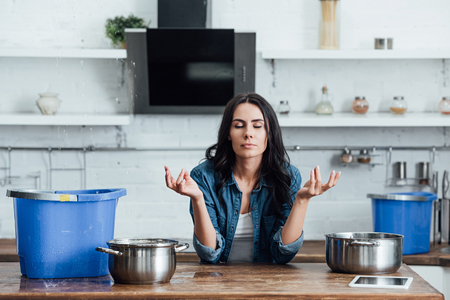 Woman trying to calm down during water damage in kitchen Banco de Imagens