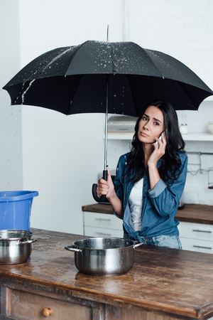 Sad woman talking on smartphone and holding umbrella under leaking ceiling in kitchen Imagens