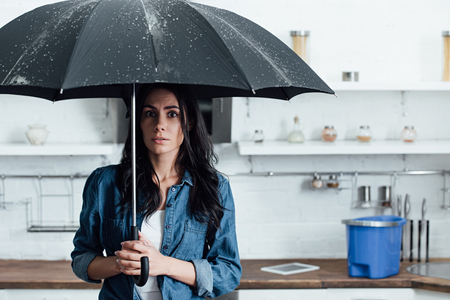 Amazed woman standing under umbrella during leak in kitchen