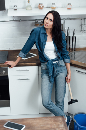 Tired woman in denim shirt holding plunger in kitchen Imagens