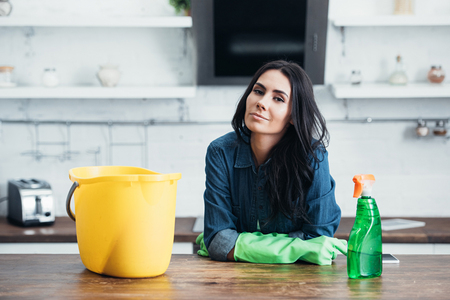 Beautiful brunette woman in rubber gloves sitting with bucket and spray in kitchen