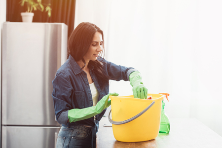 Smiling woman in green rubber gloves using bucket in kitchen Archivio Fotografico