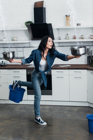 Frightened young woman with pots and buckets dealing with water leak in kitchen Imagens