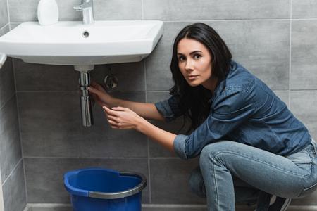 Charming brunette girl in denim shirt repairing pipe in bathroom Banco de Imagens