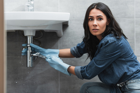 Worried woman in rubber gloves repairing pipe with wrench