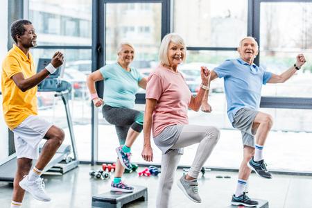 El enfoque selectivo de los atletas senior multiétnicos ejercicio sincrónico en plataformas escalonadas en el gimnasio