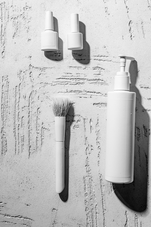 close-up view of white decorative nail polishes, brush and container on wall in beauty salon 写真素材