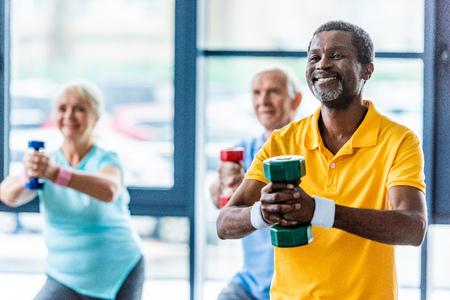 afroamerikanischer Sportler und seine Freunde trainieren mit Hanteln im Fitnessstudio Standard-Bild