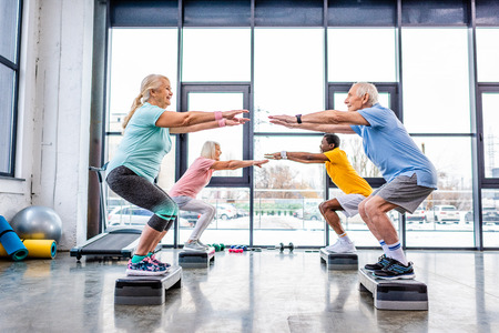 side view of happy senior multiethnic sportspeople synchronous doing squats on step platforms at gym