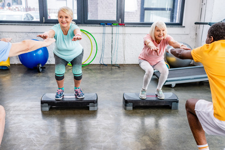 smiling senior multiethnic sportspeople synchronous doing squats on step platforms at gym Stock Photo