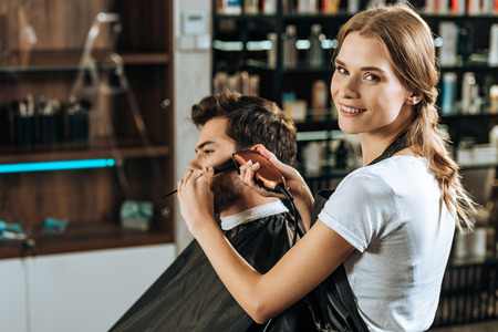 attractive hairstylist smiling at camera while trimming hair to male client in beauty salon Stockfoto
