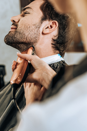 close-up partial view of hairdresser using electric hair trimmer and cutting beard to client in beauty salon