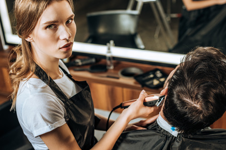 high angle view of young hairdresser using electric hair clipper and looking at camera while working with client in beauty salon Stockfoto