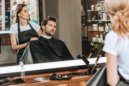 weiblicher Friseur, der im Schönheitssalon einem hübschen jungen Mann Haare schneidet