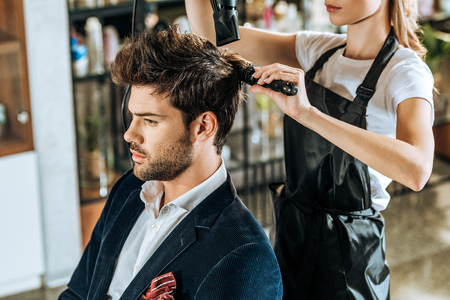 cropped shot of young hairdresser combing and drying hair to handsome client in beauty salon