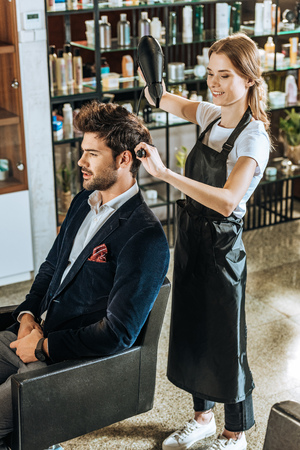 high angle view of smiling female hairdresser drying hair to handsome young man in beauty salon