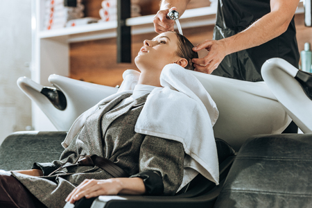 cropped shot of hairdresser washing hair to attractive young woman in beauty salon Stockfoto