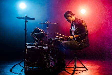 side view of male musician in leather jacket playing drums during rock concert on stage with smoke and spotlights