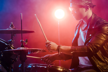 side view of young male musician in leather jacket playing drums during rock concert on stage