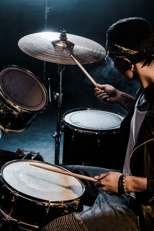 side view mixed race male musician playing drums during rock concert on stage Banco de Imagens