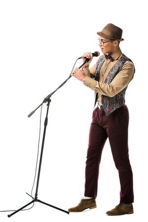 stylish young male musician in hat and eyeglasses singing in microphone isolated on white