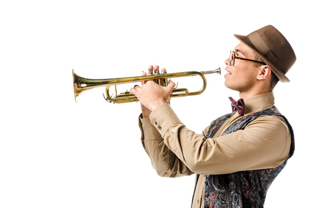 young hipster man in hat and eyeglasses playing on trumpet isolated on white