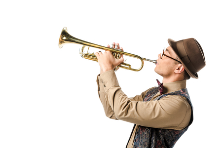 side view of mixed race male musician in stylish hat and eyeglasses playing on trumpet isolated on white
