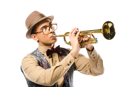 mixed race male musician in stylish hat and eyeglasses playing on trumpet isolated on white Stock Photo
