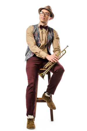 mixed race male jazzman holding trumpet and sitting on chair isolated on white Imagens
