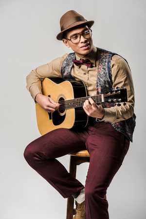stylish mixed race male musician in hat and eyeglasses playing on acoustic guitar while sitting on chair on grey Standard-Bild