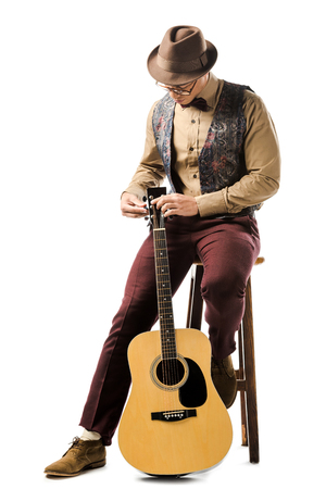 young mixed race male musician in hat and eyeglasses tuning acoustic guitar while sitting on chair isolated on white 版權商用圖片