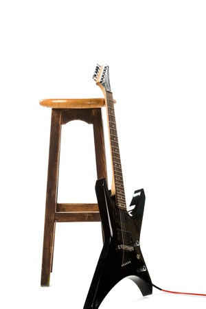 black electric guitar near wooden chair isolated on white Stock Photo