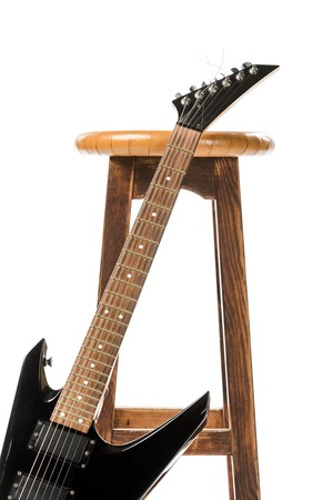 close up view of black electric guitar near wooden chair isolated on white