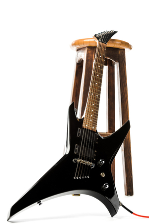 black electric guitar near wooden chair isolated on white Stock Photo - 117396225