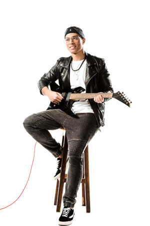smiling male rock musician in leather jacket playing on electric guitar while sitting on chair isolated on white