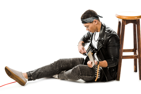 concentrated young man musician in leather jacket playing on electric guitar while sitting on floor near chair isolated on white
