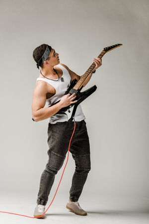 stylish mixed race male rock musician playing on electric guitar on grey