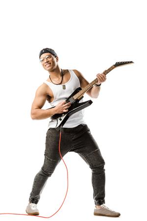glücklicher gemischter männlicher Rockmusiker, der auf E-Gitarre spielt, isoliert auf weiß Standard-Bild