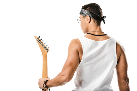rear view of young male rock musician posing with black electric guitar isolated on white
