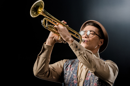 young male jazzman in hat and eyeglasses playing on trumpet isolated on black