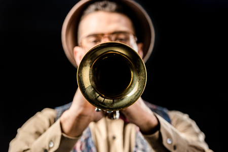 selective focus of male jazzman playing on trumpet isolated on black Stock Photo