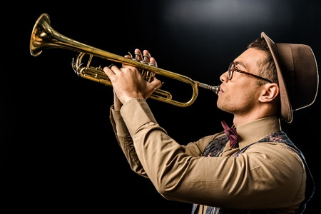 side view of young male jazzman in hat and eyeglasses playing on trumpet isolated on black