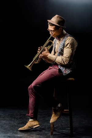stylish mixed race male musician playing on trumpet while sitting on chair on black