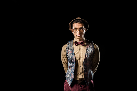 stylish young male model in vest and bow tie posing isolated on black